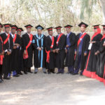 The Dean of Public Health and graduates stand shoulder to shoulder